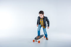 Boy in leather jacket riding skateboard on grey Royalty Free Stock Photo