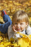 boy in leaves of autumn lies Stock Photography