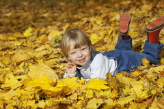 boy in leaves of autumn lies Royalty Free Stock Images