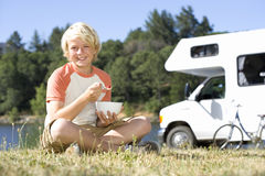 Boy (10-12) with legs crossed eating breakfast on grass, motor home in background, smiling, portrait Stock Photo