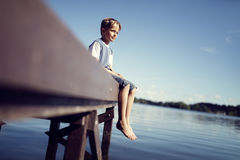 Boy with legs dangling from pier. Boy with barefoot legs and feet dangling from pier by lake on summer vacation royalty free stock images