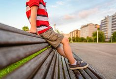Boy legs sitting on the top of bench park relaxing Royalty Free Stock Images