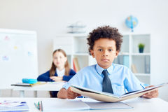 Boy at lesson of reading. Cute boy with open book sitting by desk at reading lesson Royalty Free Stock Images