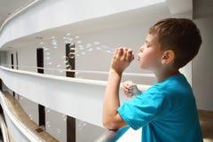 Boy lets bubbles on balcony inside large hotel. Boy in blue t-shirt lets bubbles on balcony inside large hotel royalty free stock photo