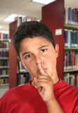 Boy in Library. A boy in the library asking for silence royalty free stock photography