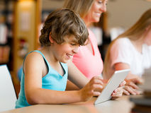 Boy in library with computer Royalty Free Stock Photos