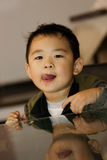 Boy licking lips. Picture of a little chinese boy licking his lips after eating cream cakes Royalty Free Stock Photos