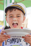 Boy licking a plate. Sailor little boy licking a plate royalty free stock photos