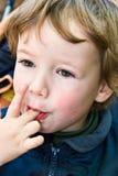Boy licks fingers Stock Photos