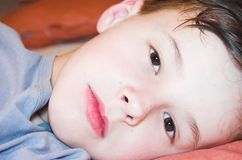 Boy lie on the bed. Young boy lie on the bed stock photo