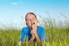 Sweet summer. Boy lie on a grass and eat sweet sugar candies royalty free stock photo