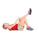 Boy lie isolated on white. Pain leg royalty free stock photography