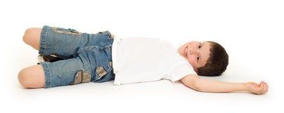 Boy lie on white. Studio isolated stock image