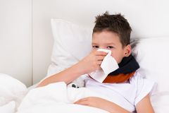 The boy lies on the bed and blows his nose in a napkin, snot after sleep. The boy lies on the bed and blows his nose in a napkin Stock Photography