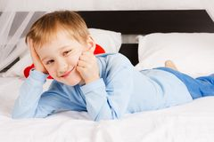 Boy  lies on a bed in a comfortable situation Stock Images