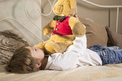 The boy lies in bed with a teddy bear. He played a favorite toy. A boy in jeans and a white shirt. Teddy bear in a red waistcoat Stock Photo