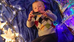 Boy playing with a car. The boy lies on a blue cloth and is played with a car in his hand stock video footage