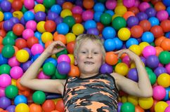 The boy lies, buried in the colorful balls of the game room. The boy lies, buried in the colorful balls of the game room Stock Images