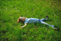 The boy lies in a dense green grass on lawn. Stock Photos