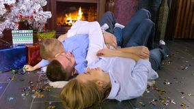 Family lies under a Christmas tree among colorful confetti. Christmas celebration concept. A boy lies on fathers chest and plays with Christmas confetti from stock video footage