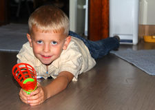 The boy lies on a floor. The little boy lies on a floor with a toy Stock Image