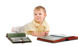 boy lies on a floor with old photo albums Royalty Free Stock Photography