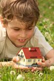 Boy lies in grass with house model in hands Stock Images