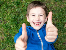 Boy lies on the grass and laughs Royalty Free Stock Image