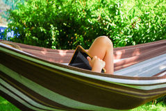 A boy lies in a hammock while using a tablet computer. A boy relaxes in a garden while lying in a hammock with a tablet computer Stock Photos