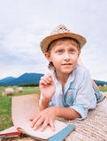 Boy lies on hay roll among the mountain field and reads a book Royalty Free Stock Photography