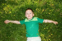 The boy lies in a meadow with outstretched arms Stock Photography