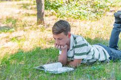 The boy lies in the park on the grass and is studying in nature, education and science, the book is lying on the grass stock photos
