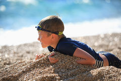 The boy lies on a pebble beach after swimming