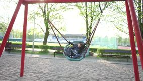 The boy lies riding on a swing. On the playground at school stock video