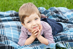 The boy lies on a rug Royalty Free Stock Photos