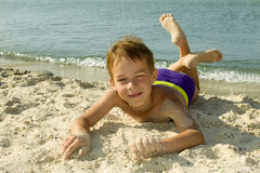 The boy lies on the sand. Royalty Free Stock Images