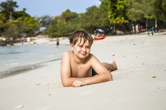 Boy lies at the sandy beach and enjoys the fine warm sand Stock Photography