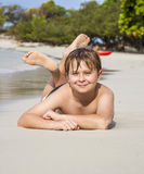 Boy lies at the sandy beach and enjoys the fine warm sand Royalty Free Stock Image