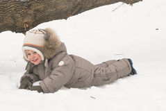 Boy lies on snow. In winter suit royalty free stock images