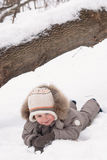 Boy lies on snow. In winter suit Stock Photos