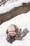Boy lies on snow. In winter suit stock photos