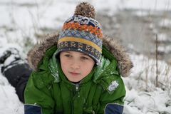 The boy lies on snow Stock Photo