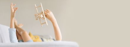 Boy lies on the sofa and plays a toy plane. Image with a larger. Copy space stock images