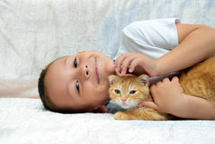 A boy lies and strokes of red kitten Stock Photography