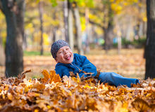 Boy lies on yellow leaves in autumn park Stock Images