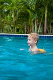 Boy in a life jacket have fun in the swimming pool royalty free stock photo