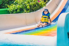 A boy in a life jacket slides down from a slide in a water park Royalty Free Stock Photo