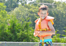 Boy with life jacket. Boy wearing a life jacket about to jump in the pool. He is excited and nervous about jumping. 6 year old boy swimming. learning to swim Royalty Free Stock Images
