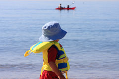 Boy with life vest. On as he looks at two kayaking Stock Photography