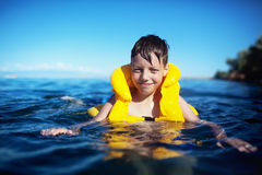 Boy in the life-vest. Smiling boy in the life-vest in the water royalty free stock photos